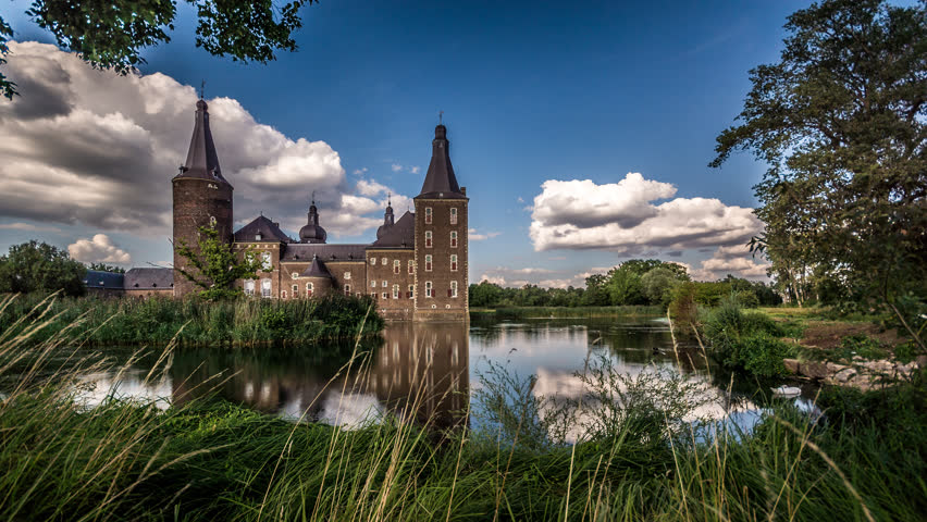 Hoensbroek Castle in the province of Limburg, The Netherlands. Time lapse footage with moving clouds, swans and geese swimming in the pond surrounding the castle.