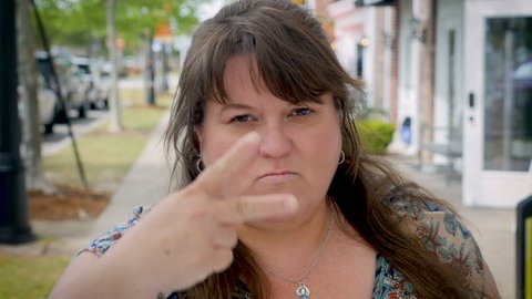 Angry mad upset curvy plus sized woman counts to three with her fingers looking at the camera in an outdoor shopping mall