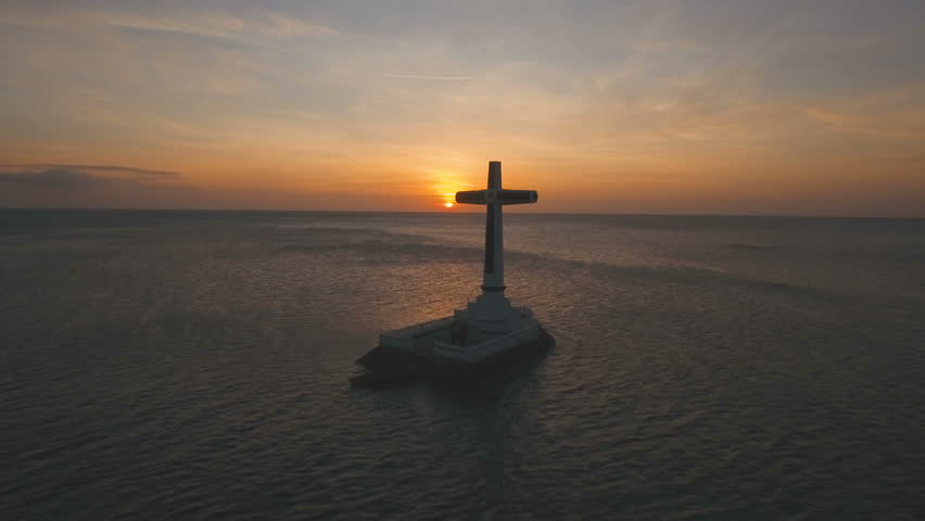 Aerial view Sunken Cemetery cross at sunset in Camiguin Island, Philippines. Large crucafix marking the underwater sunken cemetary of the coast of camiguin island near mindanao in the Philippines