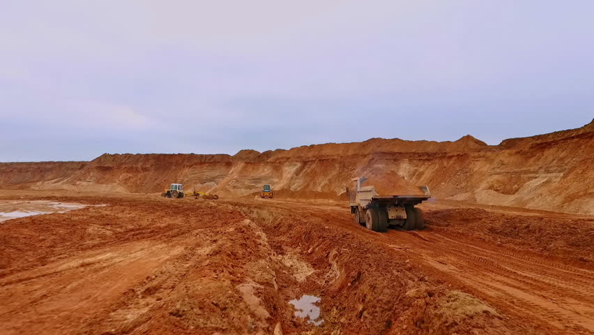 Tipper truck carries sand. Drone view of dump truck transporting sand on quarry. Aerial view dumper truck with mining sand