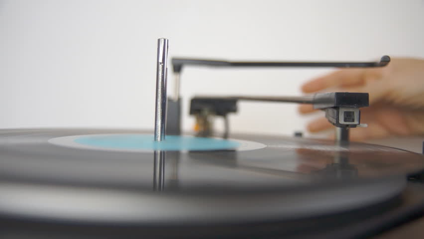 Person lowering needle to play vinyl record on retro turntable close up HD 1080p