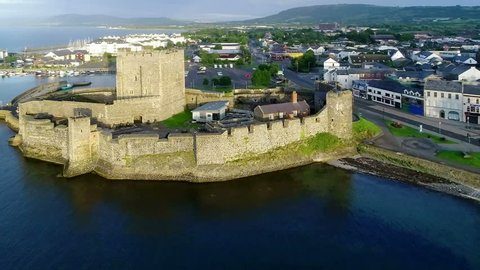 Medieval Norman Castle in Carrickfergus near Belfast in sunrise light. Aerial video with marina, yachts, parking, town and far view of Belfast in the background