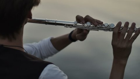 closeup of flutist playing in the sunset near water