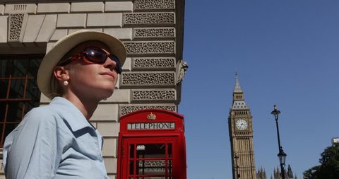 4K Businesswoman relaxed near Big Ben Tower, British telephone by day, London tourist