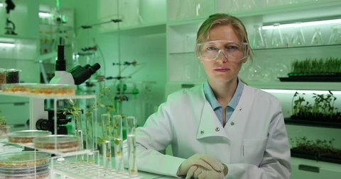 4K Researcher woman looking camera, serious posing talking interview report tests