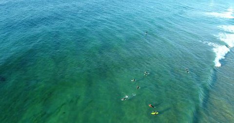 Wave surfers catching the rolling wave at Mona Vale northern beaches of Sydney in aerial view.