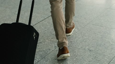 Close up shot of man legs with the baggage walking to the airport terminal.