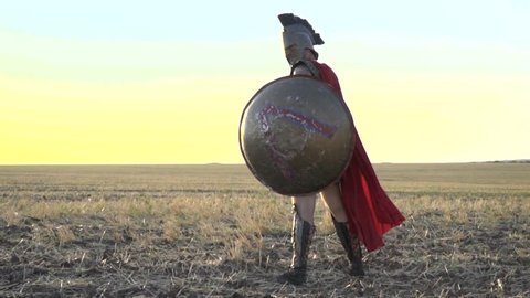 The majestic Roman legionary with a shield in his hand is standing in the field while in the wind his red cloak is blowing, slow motion