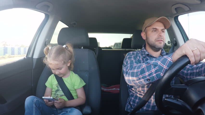 The father and his little daughter are driving in the car. A little girl is playing on a smartphone in the seat of a car. Man texting and driving with his daughter in the car.