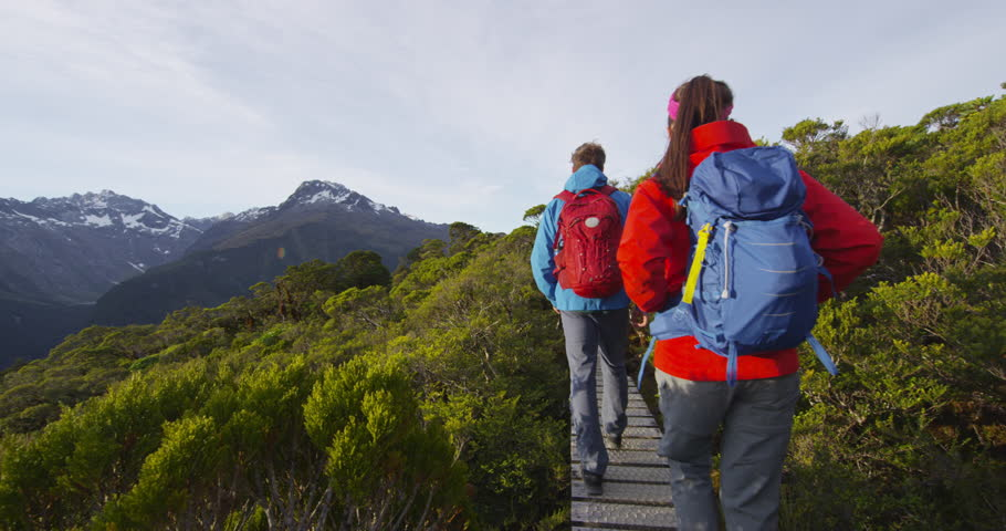 Backpackers hiking at sunset by mountains on famous Routeburn Track, New Zealand in Fiordland National Park during sunny day. Young backpackers walking. Hikers are tramping on Key Summit Track