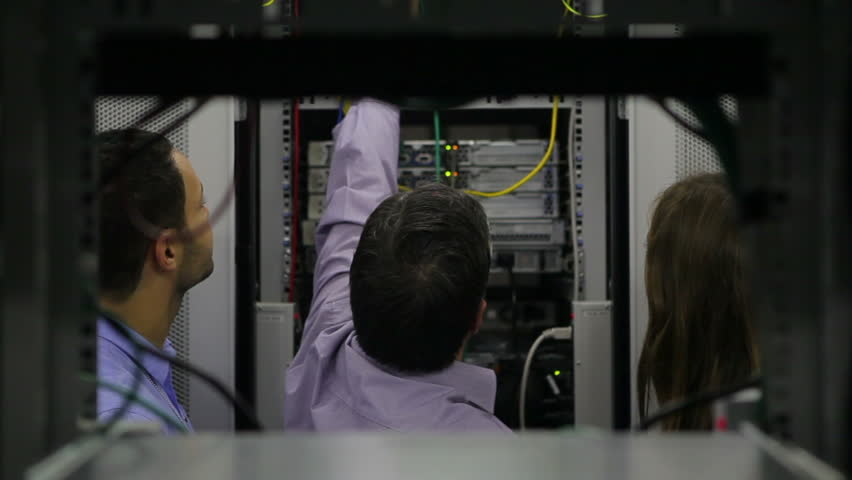 Two persons watching man while fixing wires in hallway of data center | Shutterstock HD Video #2975644