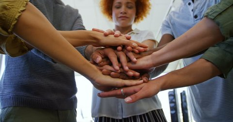 Team of business people forming hand stack in office