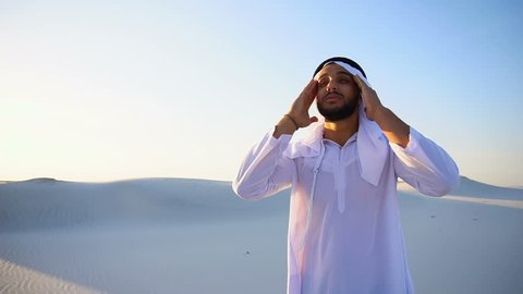 Portrait of tired Arab man, who holds head and feels migraine, tries to calm pain and massages whiskey, standing in middle of bottomless desert with snow-white sand on sunny summer day. Swarthy Muslim