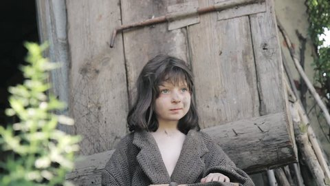 poor small girl cries near wooden door. orphan girl from european country. small cinderella girl