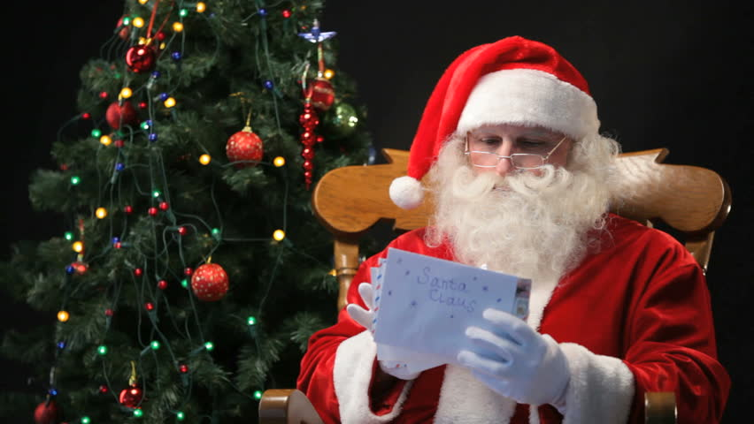 Santa Claus sitting in the chair and reading Christmas letters sent by children