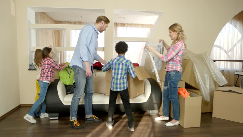 Family unpacking things from boxes. Kids and parents indoors. Pros and cons of renting.