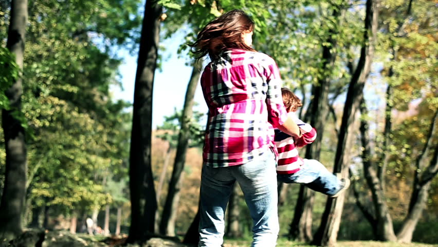 Young mother having fun with her son in beautiful autumn park, slow motion  | Shutterstock HD Video #2980033