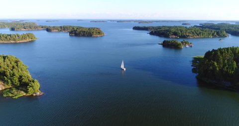 Sailboat in archipelago, Cinema 4k aerial view away from a sail boat, in uusimaa saaristo archipelago, on the gulf of finland, on a sunny evening dawn, in Raasepori, Finland