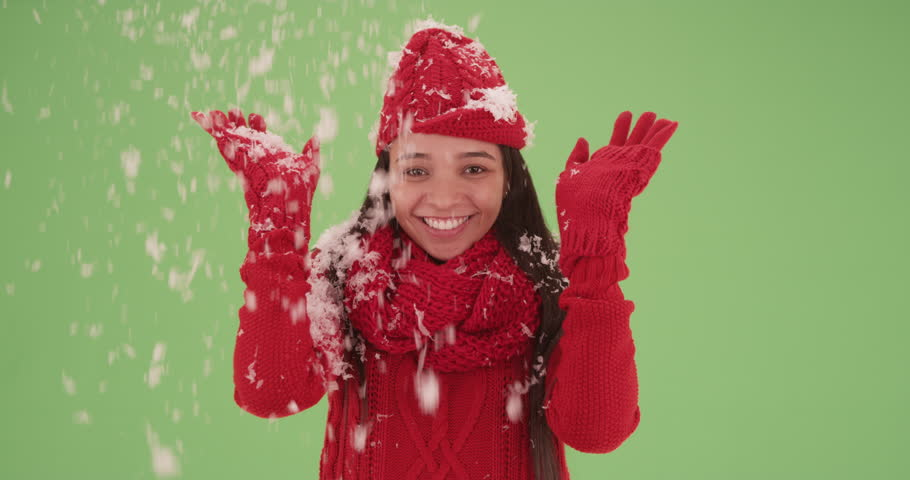 Smiling Hispanic girl with snow falling on her on green screen. On green screen to be keyed or composited.