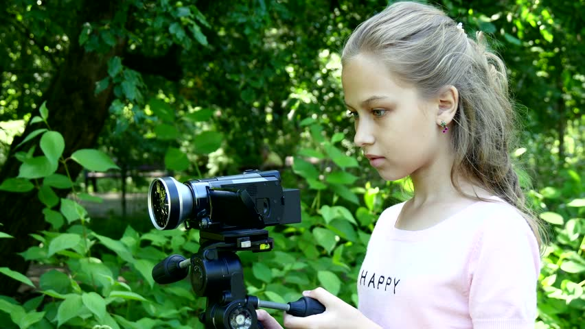 Young girl looks into video camera on background of green park background. Children outdoors in summer are creative work of cinema. Beautiful footage for family. Interesting world in childhood.   Shutterstock HD Video #29827780