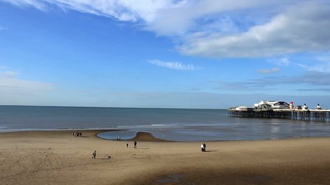 People on the beach - North Pier Blackpool. Blackpool is a popular seaside resort on the Lancashire coast in North West England.