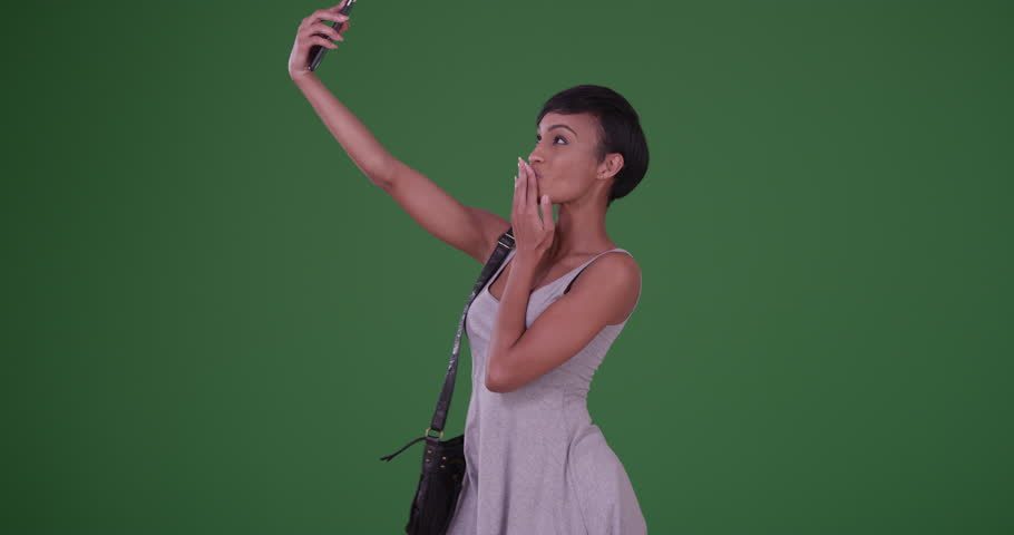 Woman blowing kiss and taking a selfie picture with smartphone on green screen. On green screen to be keyed or composited.