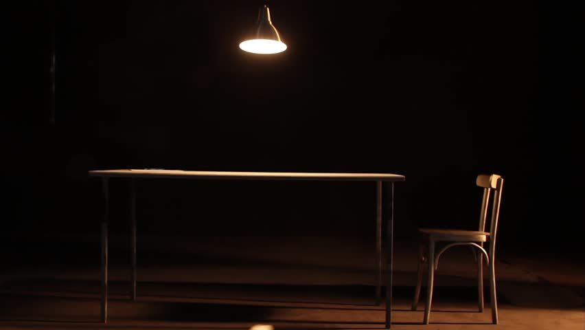Metallic Lamp Oscillating Slowly Above A Large Wooden Table In Darkened Room