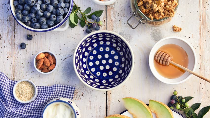 Granola with natural yogurt, fresh blueberries, nuts and honey, delicious breakfast or dessert, top view.  Healthy eating concept. Stop motion animation.