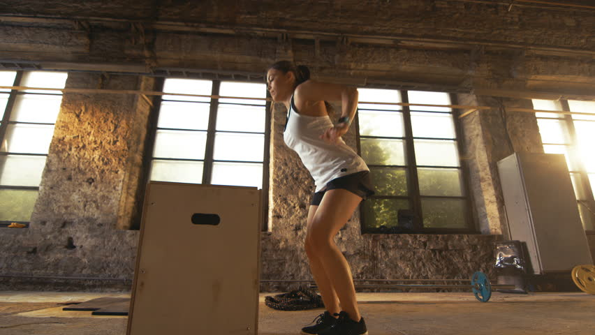 Fit Athletic Woman Does Box Jumps in the Deserted Factory Gym. Intense Exercise is Part of Her Daily Cross Fitness Training Program. Shot on RED EPIC-W 8K Helium Cinema Camera. | Shutterstock HD Video #29872960