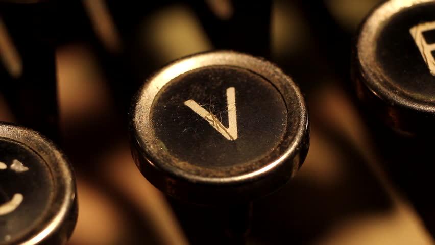 "A male finger presses the letter ""V"" key on an old typewriter."