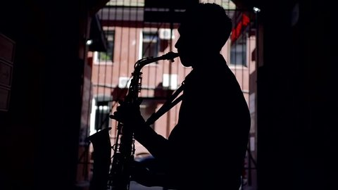 silhouette of a young musician saxophonist. play a wind musical instrument on the street in the tunnel of the building