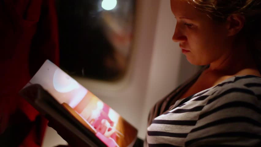 Young woman sits in chair near illuminator of airplane and turns pages of magazin during fly