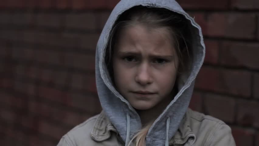 Refugee homeless child. Dark portrait of preteen girl standing in front of brick wall, she is looking unhappy and angry.