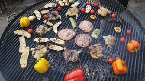 Top View of the Cooking of Meat and Vegetables on the Grill. Barbecue delicious, Browned Sausages, chicken, bell pepper, eggplant, tomatoes are fried on a barbecue. Outdoor cooking.