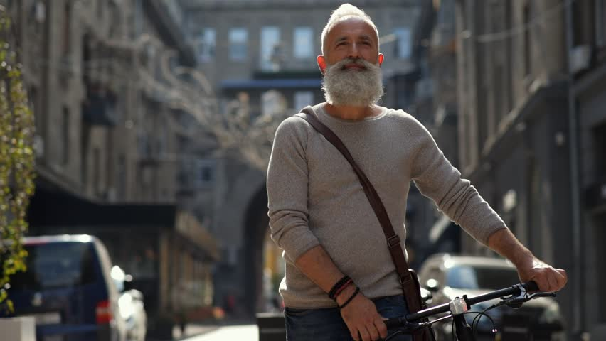 Active older man walking down street with bicycle | Shutterstock HD Video #29936950