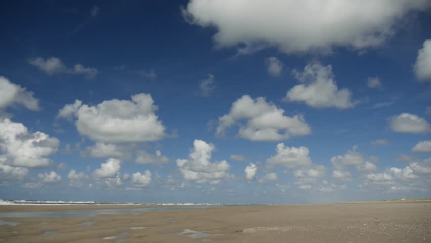 time lapse: a panoramic view of the sandy beach near the village of Terschelling, Frisian islands, Holland with white clouds in the blue sky