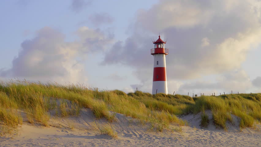 Red an white lighthouse on top of an s sand dunes in beautiful sunset light on the german holiday island sylt  | Shutterstock HD Video #29947900