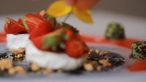 A delicious creative foodie gourmet Goat Cheese and Strawberries, granola, kale. Meal is being given the finishing touches by the chef cook presentation in a restaurant or hotel kitchen cuisine.