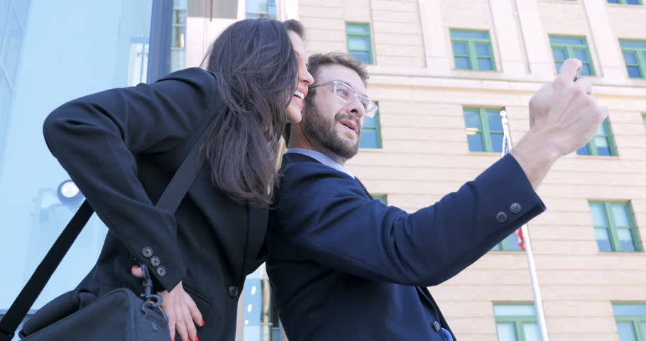 Two young 30s coworkers take a selfie outside skyscrapers with an American flag handheld in 4k | Shutterstock HD Video #29992510