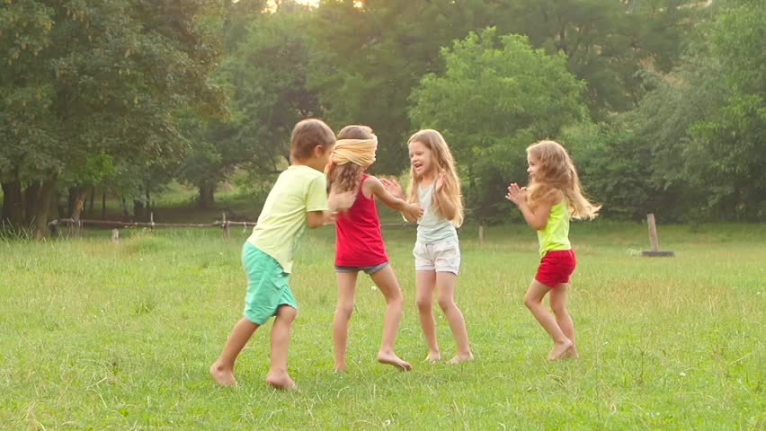 Happy group of little friends playing and clapping together outdoors in the summer. Slow motion