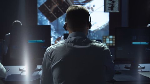 Movement shot back view of man working on space mission in control center. Observing the flight of a satellite in orbit. Elements of this image furnished by NASA.