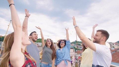 Festive Group Of Diverse Pretty Young Friends Standing In A Circle High Five Celebrating Victory And Teamwork Success And Colaboration Fun Time At Party Carefree Friendship Cheerful Artsy Lifestyle