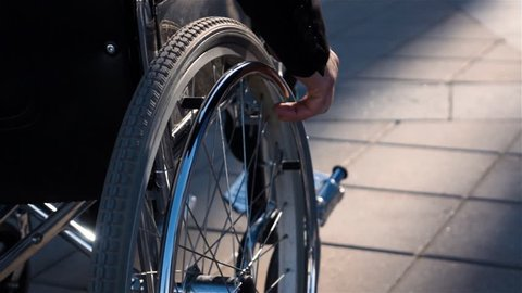 Rear view of a disabled man in wheelchair near business centre with focus on hand. He employee or businessman, moving to his work office. Slow motion shot 250 fps.