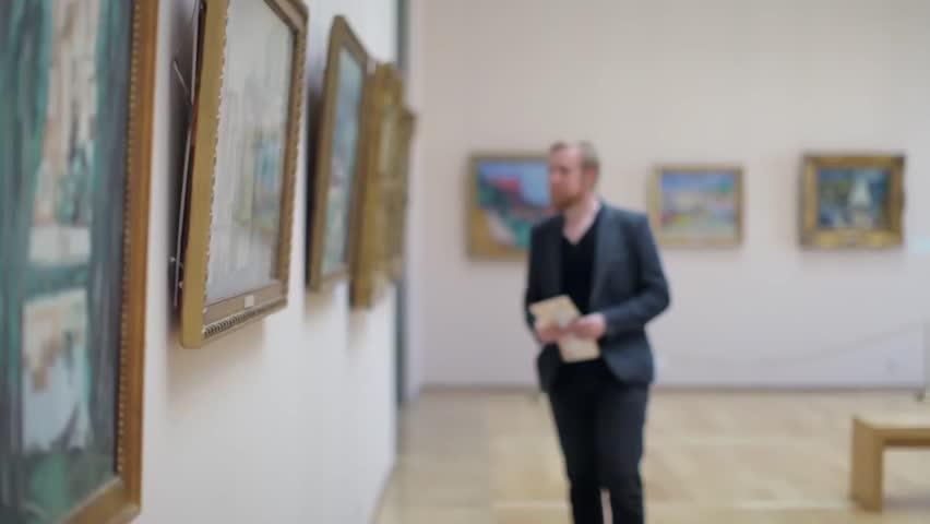Man in a Suit Looks at a Picture in a Museum