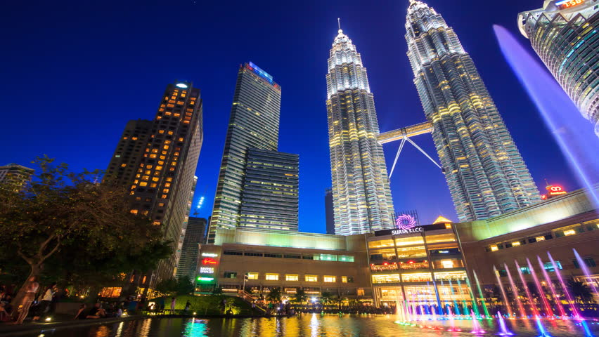 KLCC PARK, MALAYSIA - JULY 26 2017 : Day to Night Twin Towers And KLCC Park Symphony Fountain Lake Show Every Evening, Landmark Travel Place of Kuala Lumpur, Malaysia 4K Time Lapse (doly pan shot)
