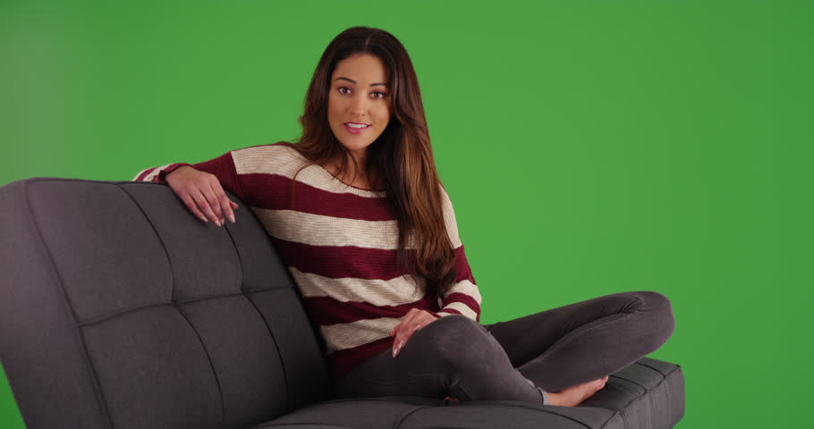 Portrait of cute Latina female lounging on couch, smiling at camera on green screen. On green screen to be keyed or composited. | Shutterstock HD Video #30031660