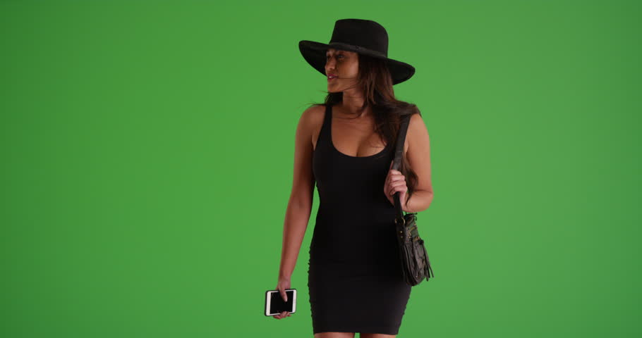 Young Latina woman in dress and hat walking toward the camera holding her smart phone in slow motion on green screen. On green screen to be keyed or composited.