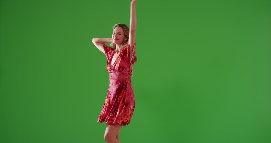 Attractive middle aged Caucasian woman in sundress dancing on green screen. On green screen to be keyed or composited.