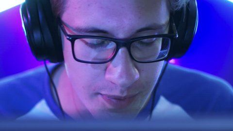 Professional Gamer Plays in MMORPG/ Strategy/ Shooter Video Game on His Computer. He's Participating in Online Cyber Games Tournament, Plays at Home, or in Internet Cafe. He Wears Glasses and Headset.