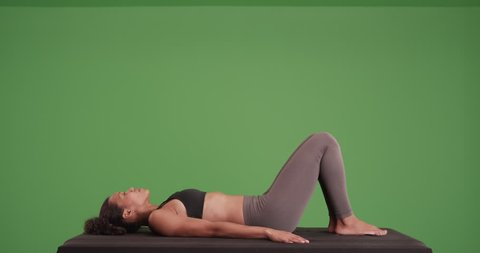 Isolated mixed race woman athlete doing hip raises on matt on green screen. On green screen for keying or compositing.